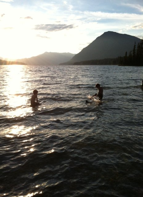 brothers floating on logs at sunset