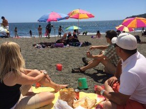 Enjoying empenadas on the beach while the kids play